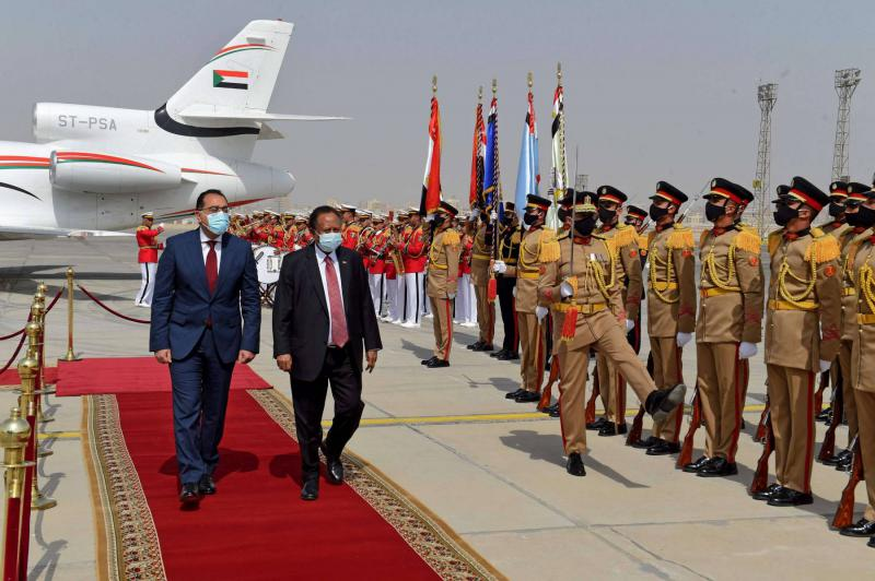 Egyptian Prime Minister Mostafa Madbouly (L) welcomes his Sudanese counterpart Abdalla Hamdok upon his arrival in the Egyptian capital Cairo, on March 11, 2021. (AFP)