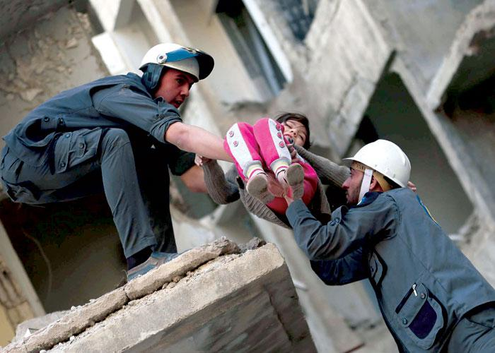 A 2016 picture shows members of the Syrian Civil Defence evacuating a child in the rebel-held eastern Ghouta area, east of the capital Damascus. (AFP)