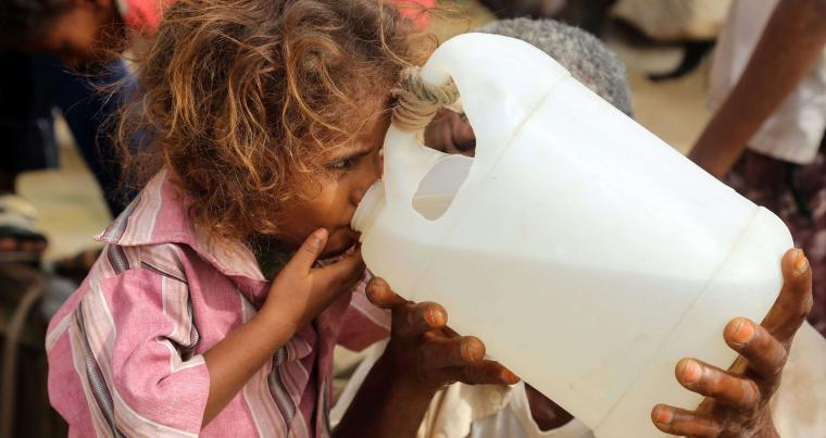 A Yemeni girl drinks water collected from a well in an impoverished village on the outskirts of the port city of Hodeidah. (AFP)