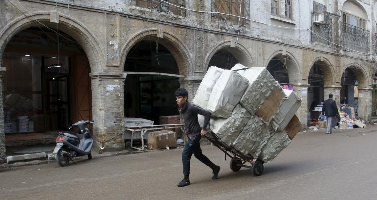 Limited opportunities. A worker pulls a cart loaded with goods at a market in Baghdad.          (Reuters)