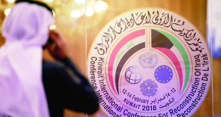 A Kuwaiti journalist speaks on his phone in front of the logo of the Iraq reconstruction conference in Kuwait City, on  February 11. (AFP)