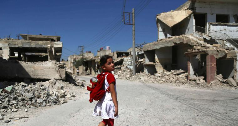 A Syrian girl walks down a destroyed street as she heads to school in Eastern Ghouta's town of Douma, last September. (AFP)
