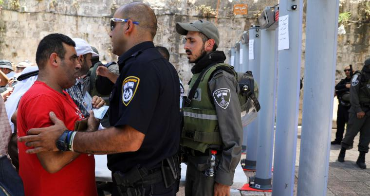 An Israeli police officer checks the identity of a Palestinian man next to newly installed metal detectors in Jerusalem's Old City, last July . (Reuters)