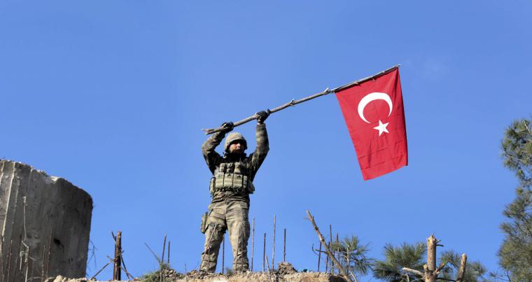 A soldier waves a Turkish flag as Turkish troops secure Bursayah hill, on Januaty 28. (AP)
