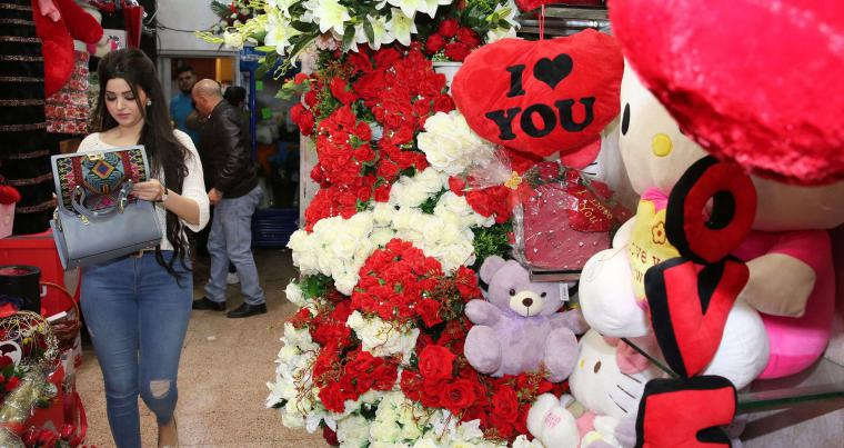 An Iraqi woman walks past Valentine's Day decorations in Baghdad, on February 14. (AFP)