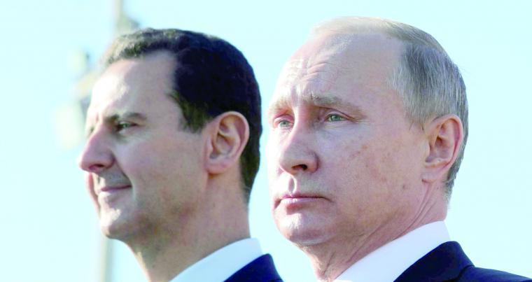 Russian President Vladimir Putin (R) and Syrian President Bashar Assad watch troops marching at the Hmeimim Air Base in Syria. (AP)