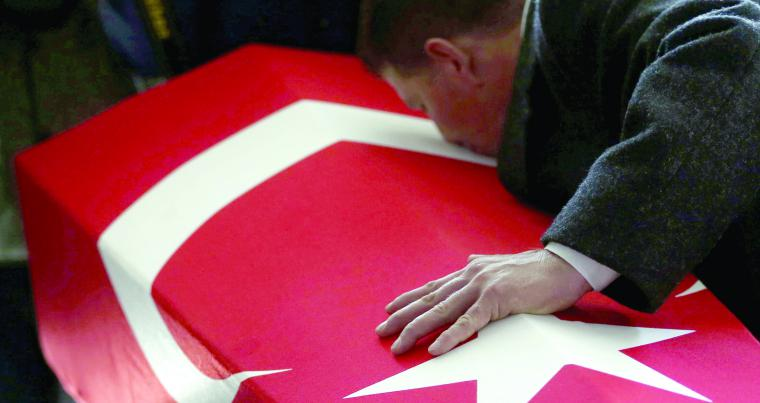 A family member kisses the flag-covered coffin of a Turkish soldier after his funeral prayers in Izmir, on February 11.	(AP)