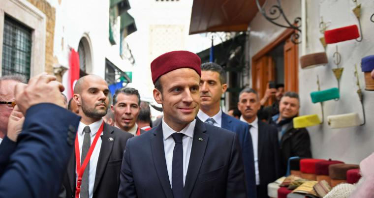 French President Emmanuel Macron (C) tries on a chechia during his tour of the Medina (old town) of the Tunisian capital Tunis on February 1.  (AFP)