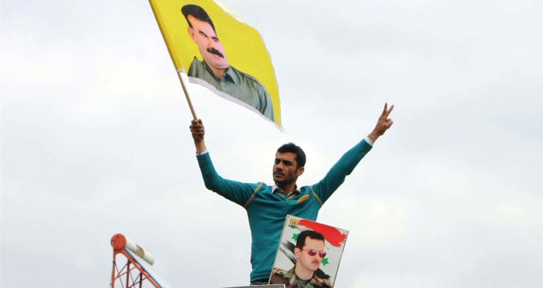 People wave the Syrian flag and portraits of President Bashar Assad and Kurdistan Workers' Party (PKK) leader Abdullah Ocalan as a convoy of pro-Syrian government fighters arrives in Afrin, on February 22.(AFP)
