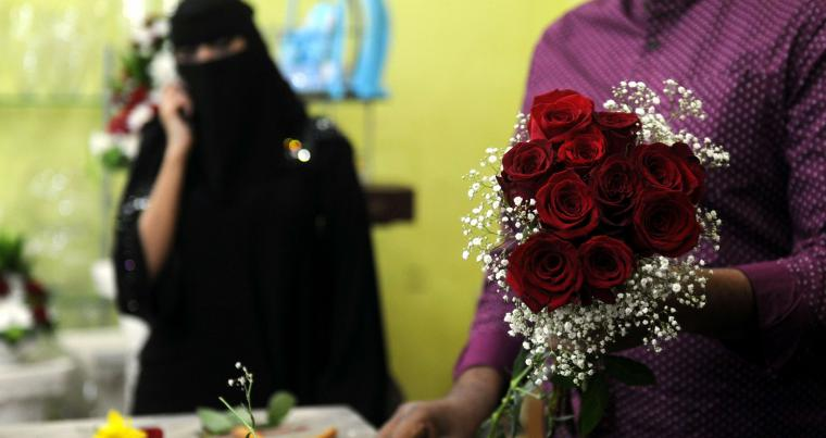 A florist prepares a Valentine's Day bouquet of flowers for a customer at a flower shop in Jeddah, on February 14.  (AFP)