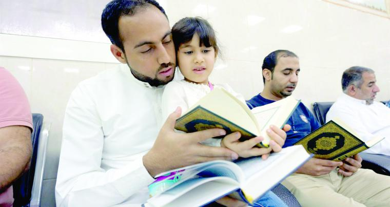 A Saudi man and a child read a copy of the Quran, Islam's holy book, inside a mosque.(AFP)