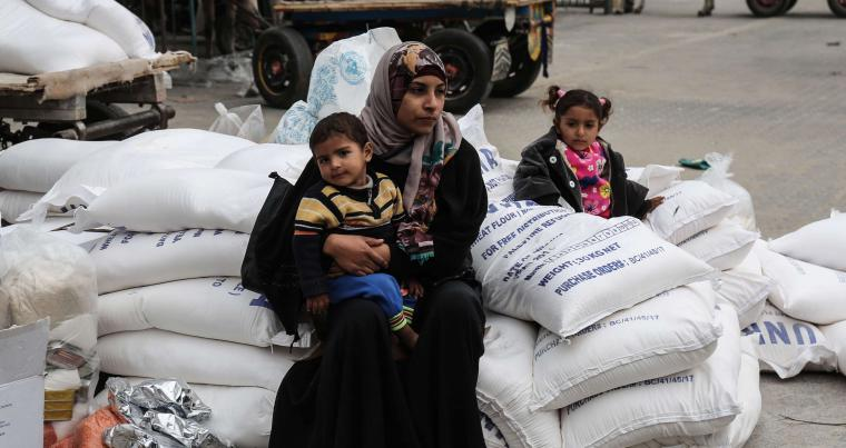 A Palestinian woman sits with a child after receiving food supplies from the United Nations' offices in the Khan Yunis refugee camp in the southern Gaza Strip, on February 11. (AFP)