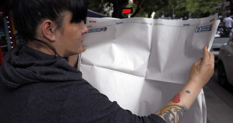 A Turkish woman poses with a blank copy of the opposition Sozcu newspaper in protest against detentions, last May. (AP)