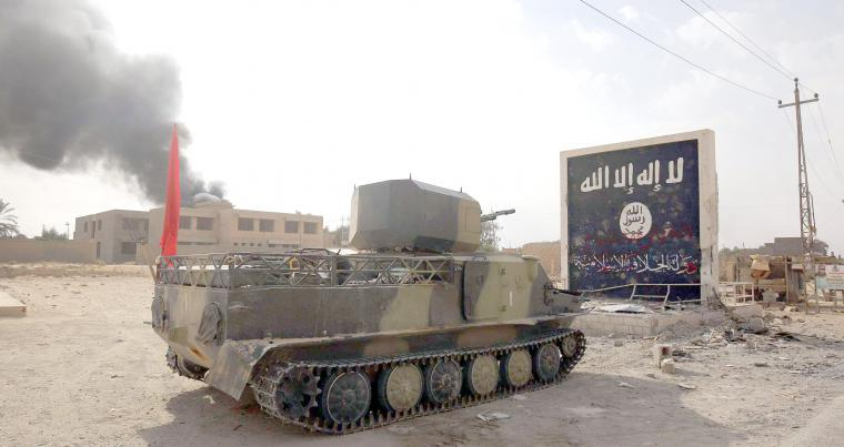 An Iraqi forces' tank faces an ISIS mural in the city of al-Qaim in Iraq's western Anbar province near the Syrian border. (AFP)
