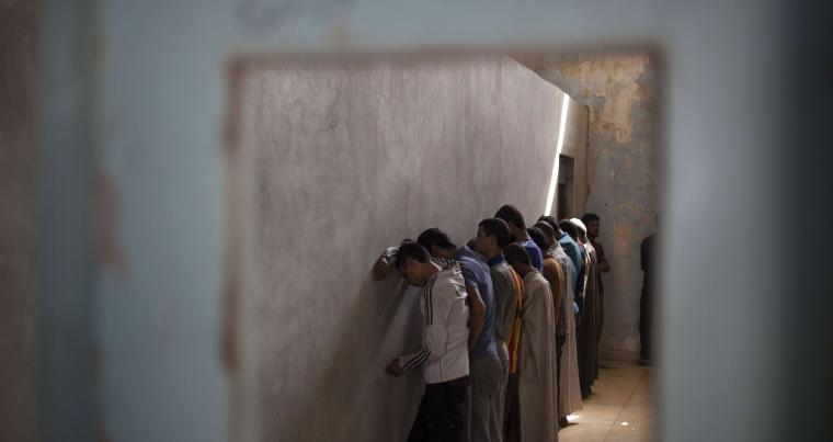 Suspected ISIS militants stand facing a wall in order not to see security officers at a Kurdish screening centre in Dibis, last October. (AP)