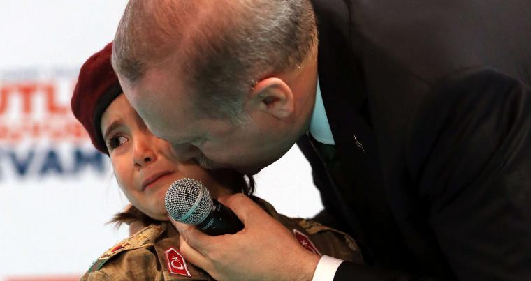 Turkish President Recep Tayyip Erdogan kisses Amine Tiras, a young girl in military uniform, as he speaks to his ruling party members in Kahramanmaras, on February 24. (AP)