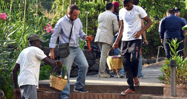 People carry vegetable baskets inside a camp for migrant minors in Catania. (AFP)