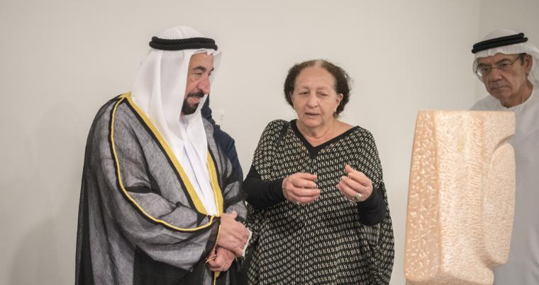 Ruler of Sharjah Sheikh Sultan bin Mohammed al-Qasimi (L) listens to artist Mona Saudi at the official opening of her exhibition.    (Sharjah Art Foundation)