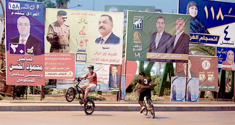 Campaign posters for parliamentary elections adorn a street in Baghdad, on April 19. (AP)