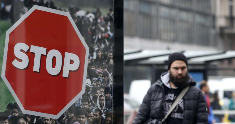 A man walks by an anti-migration billboard placed on a street in Budapest. (AP)