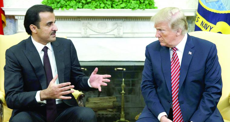 US President Donald Trump (R) listens to Qatari Emir Sheikh Tamim bin Hamad  al-Thani during a meeting in Washington, on April 10.  (AP)