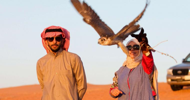 A Saudi woman releases a falcon at Al-Reem Reserve camp, west of Riyadh. (Reuters)