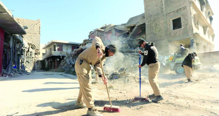 Workers clean the street in Mosul, on January 10. (Reuters)