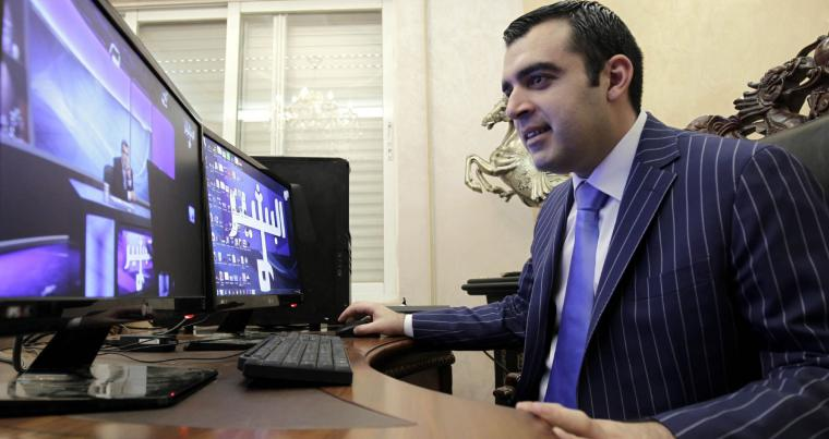 "Iraqi Ahmad al-Basheer, host of the ""Basheer Show,"" watches a video of his TV show on a computer screen in Amman. (AFP)"