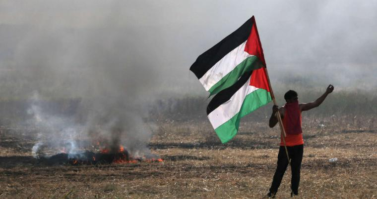 A protester holding Palestinian flags during clashes with Israeli troops near Gaza's border with Israel, on April 5. (Reuters)