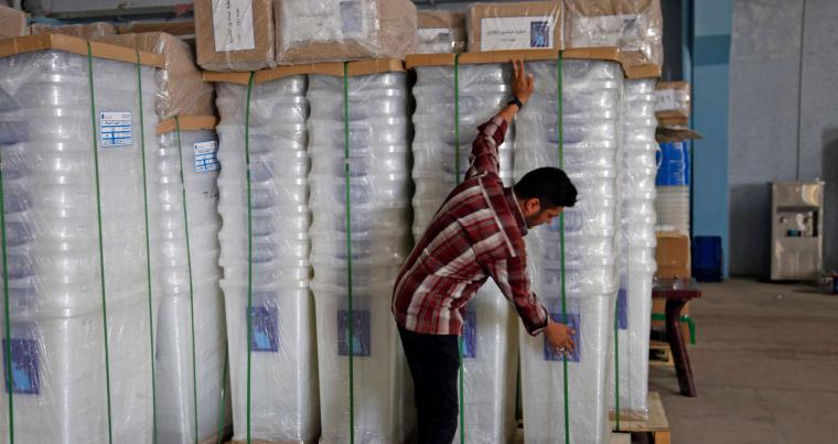 Staked up issues. A member of Iraq's electoral commission arranges boxes ahead of the parliamentary elections at a warehouse in Najaf, on April 19. (AFP)
