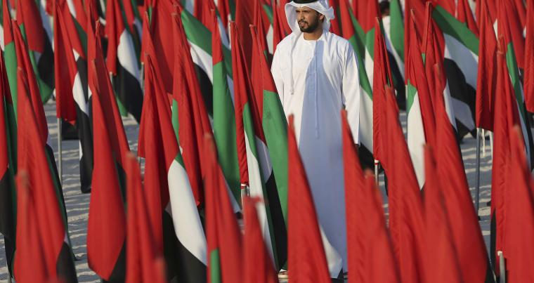 A young Emirati man walks through national flags on diplay in Dubai. (AP)
