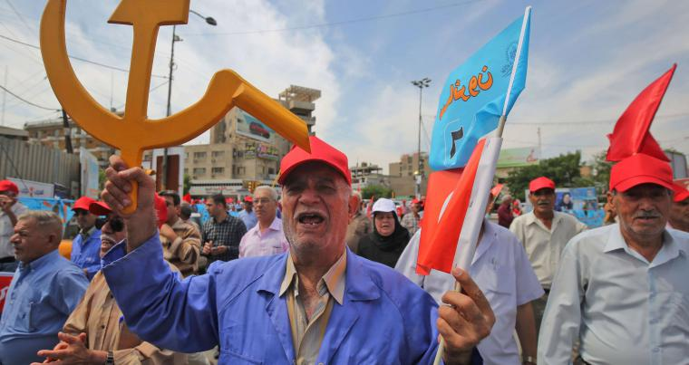 A supporter of the Iraqi Communist Party holds the communist symbol of the hammer and sickle during a march in Baghdad.   (AFP)