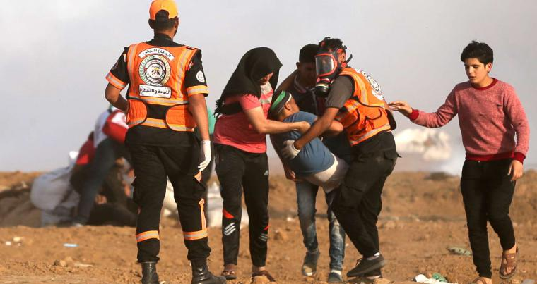 Palestinians carry an injured protester during clashes with Israeli forces along the border with Gaza, on May 18. (AFP)