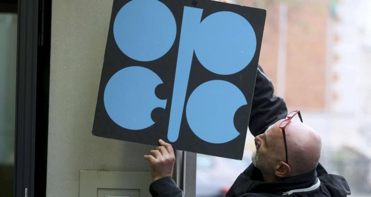 A worker attaches an OPEC poster at the organisation's headquarters in Vienna. (AP)