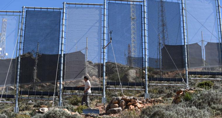 A Moroccan man inspects fog fences in a hamlet on the outskirts of the southern coastal city of Sidi Ifni, in 2015. (AFP)