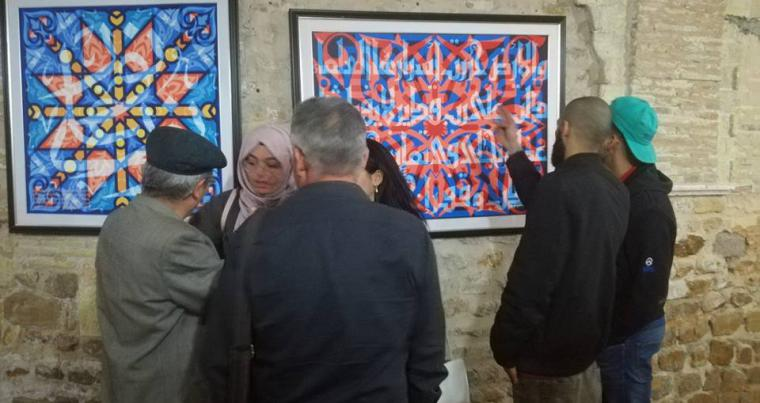 "Visitors look at paintings at the ""Dwaya"" exhibition in Tunis. (Breaking the Ice)"