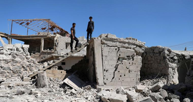 Men inspect a damaged house in Busra al-Harir town, near Deraa, Syria, on March 13. (Reuters)