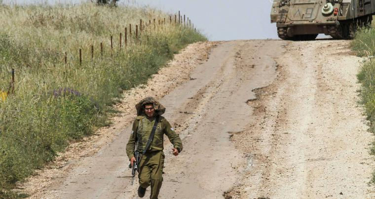 An Israeli soldier runs to direct an armoured personal vehicle near the Syrian border in the Golan Heights, on May 10. (AFP)