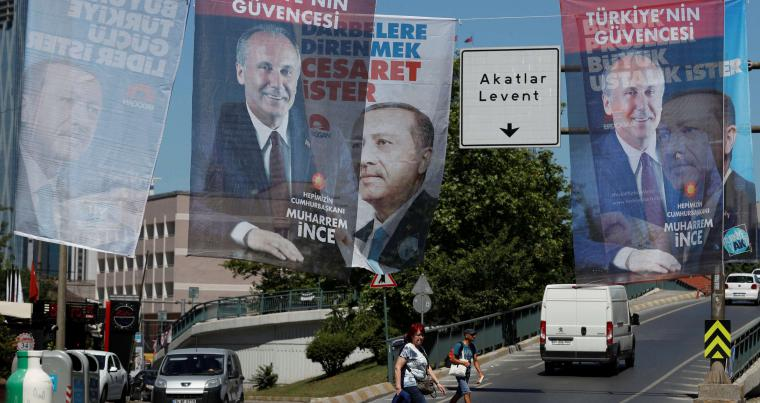 Eclipsed popularity. People walk under election posters for Turkish President Recep Tayyip Erdogan and presidential candidate Muharrem Ince in Istanbul, on June 13. (Reuters)