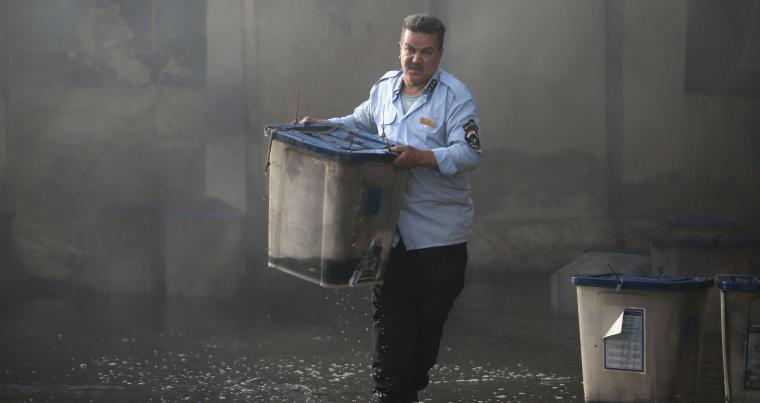 An Iraqi official carries a ballot box after a fire at a storage site in Baghdad, housing the boxes from Iraq's May parliamentary election, on June 10. (Reuters)