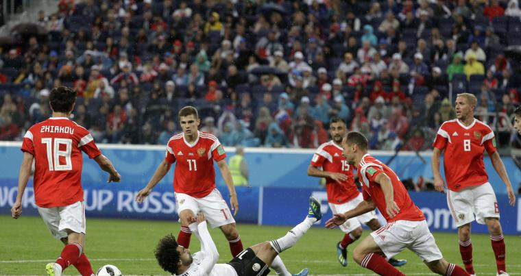 Russia's Mario Fernandes (L) challenges for the ball Egypt's Mohamed Salah, during the group A match between Russia and Egypt at the 2018 soccer World Cup in St. Petersburg, Russia, on June 19. (AP)