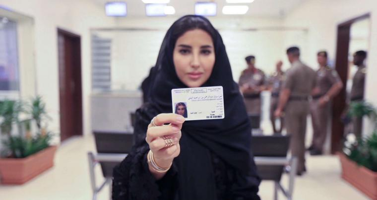 Saudi national Esraa Albuti, an Executive Director at Ernst & Young, displays her brand new driving license, at the General Department of Traffic in Riyadh, on June 4. (Saudi Information Ministry via AP)