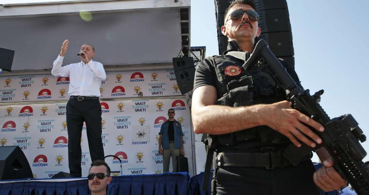 Under the watchful eye of a Turkish special police officer, President Recep Tayyip Erdogan delivers a speech  in Yalova, Turkey. (AP)