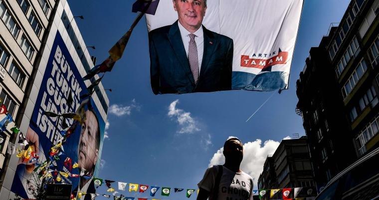 A man walks past banners of Turkey's main opposition party presidential candidate Muharrem Ince (top) and Turkish President Recep Tayyip Erdogan (L) in Istanbul on June 20, 2018. (AFP)