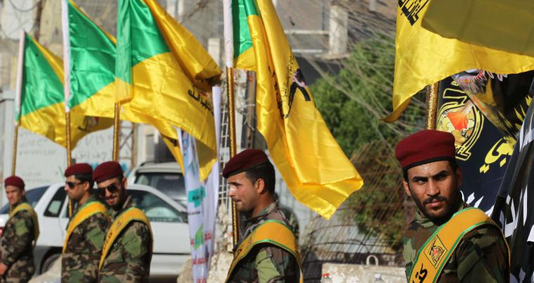 Dangerous bribes. Members of the Iraqi Hezbollah Brigades carry flags during a ceremony in Baghdad, last June.                                                      (AFP)