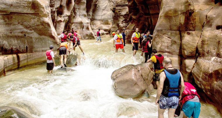 A group of adventurers battle raging waters at Wadi Mujib. (Wild Jordan)