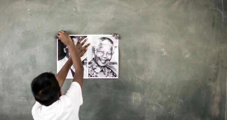 A child sticks a poster of former South African President Nelson Mandela on the chalkboard in Durban, on July 18. (AFP)