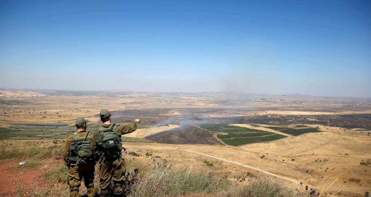 Israeli soldiers look at the Syrian side of the border on the Israeli-occupied Golan Heights, on July 7. (Reuters)