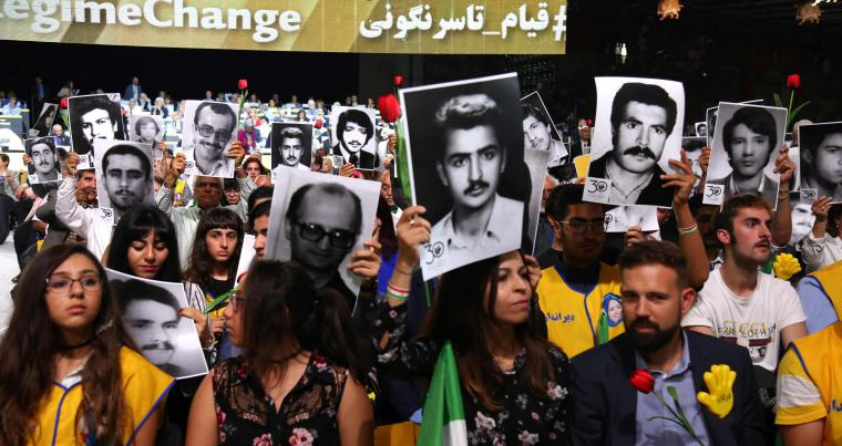 "Iranians hold pictures of relatives killed by their regime, during ""Free Iran 2018 - the Alternative"" event in Villepinte, north of Paris, on June 30. (AFP)"