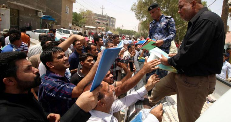 Iraqi protesters hand over job requests to government employees in Basra, on July 18. (Reuters)